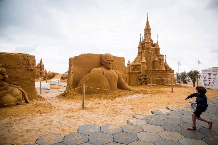 A child stands next to sand sculptures representing Iron man and others characters and scenes of Disney movies during an exhibition Disney Sand Magic in Ostend on June 29, 2017. (AFP Photo/ Aurore Belot)