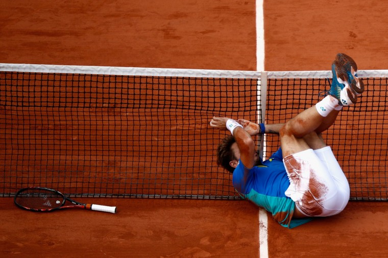 Stan Wawrinka of Switzerland falls into the net after playing a shot during men's singles quarter finals match against Marin Cilic of Croatia on day eleven of the 2017 French Open at Roland Garros on June 7, 2017 in Paris, France. (Photo by Adam Pretty/Getty Images)