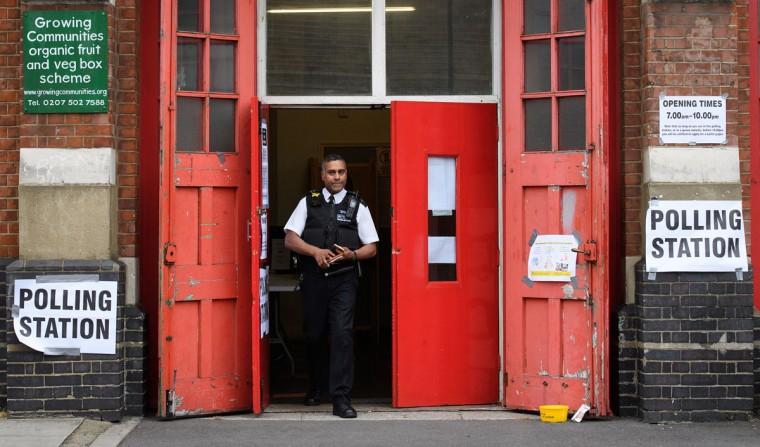 LONDON, UNITED KINGDOM - JUNE 08: A police officer visits the polling station within a former fire station on June 8, 2017 in London, United Kingdom. Polling stations have opened as the nation votes to decide the next UK government in a general election. (Photo by Leon Neal/Getty Images)