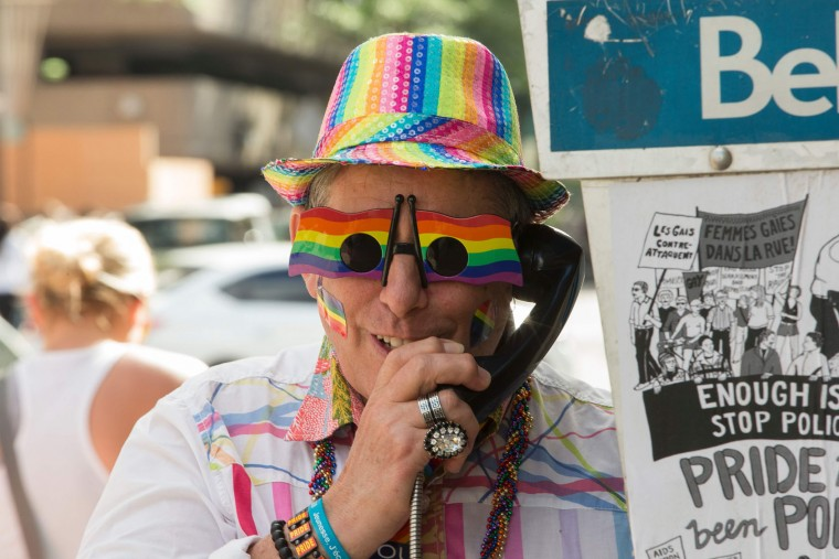 A man with Pride glasses talks on a pay phone during the Pride Parade in Toronto, Ontario, June 25, 2017. The event draws hundreds of thousands of spectators every year. (Geoff Robins/AFP/Getty Images)