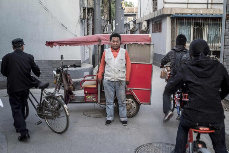 This photo taken on April 22, 2017 shows a rickshaw driver (C) posing in Beijing. Appearing in China at the end of the 19th century, rickshaws originally had two wheels and were pulled by their driver on foot, with passengers seated at the back. Today, most of the vehicles are tricycles - some still have pedals and are propelled by physical force, but the majority are equipped with electric or gas engines. (FRED DUFOUR/AFP/Getty Images)