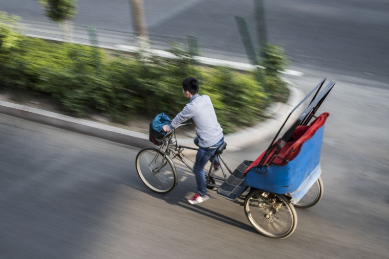 This photo taken on April 23, 2017 shows rickshaw driver Li Wei riding in the streets of Beijing. Appearing in China at the end of the 19th century, rickshaws originally had two wheels and were pulled by their driver on foot, with passengers seated at the back. Today, most of the vehicles are tricycles - some still have pedals and are propelled by physical force, but the majority are equipped with electric or gas engines. (FRED DUFOUR/AFP/Getty Images)