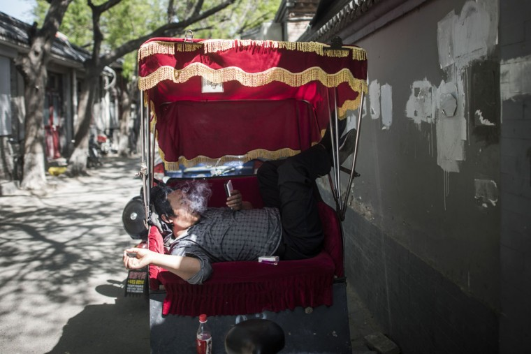 This photo taken on April 23, 2017 shows a rickshaw driver taking a rest during lunch time in Beijing. Appearing in China at the end of the 19th century, rickshaws originally had two wheels and were pulled by their driver on foot, with passengers seated at the back. Today, most of the vehicles are tricycles - some still have pedals and are propelled by physical force, but the majority are equipped with electric or gas engines. (FRED DUFOUR/AFP/Getty Images)