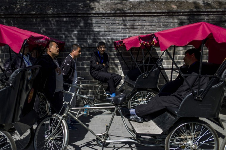 This photo taken on April 24, 2017 shows rickshaw drivers waiting for customers in a touristic area in Beijing. Appearing in China at the end of the 19th century, rickshaws originally had two wheels and were pulled by their driver on foot, with passengers seated at the back. Today, most of the vehicles are tricycles - some still have pedals and are propelled by physical force, but the majority are equipped with electric or gas engines. (FRED DUFOUR/AFP/Getty Images)