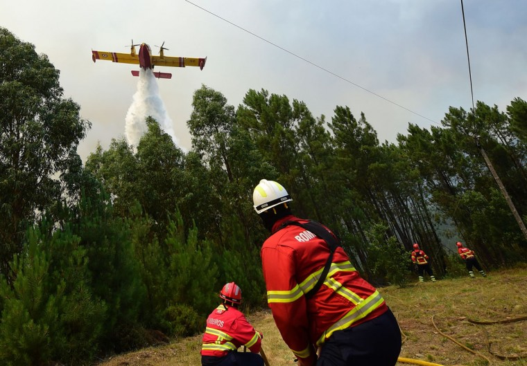 Some firefighters prepare themselves to be overflied by a Canadair firefighting plane droping its water load on a wildfire in Vale da Ponte, Pedrograo Grande, on June 20, 2017. The huge forest fire that erupted on June 17, 2017 in central Portugal killed at least 64 people and injured 135 more, with many trapped in their cars by the flames. (Miguel Riopa/AFP/Getty Images)