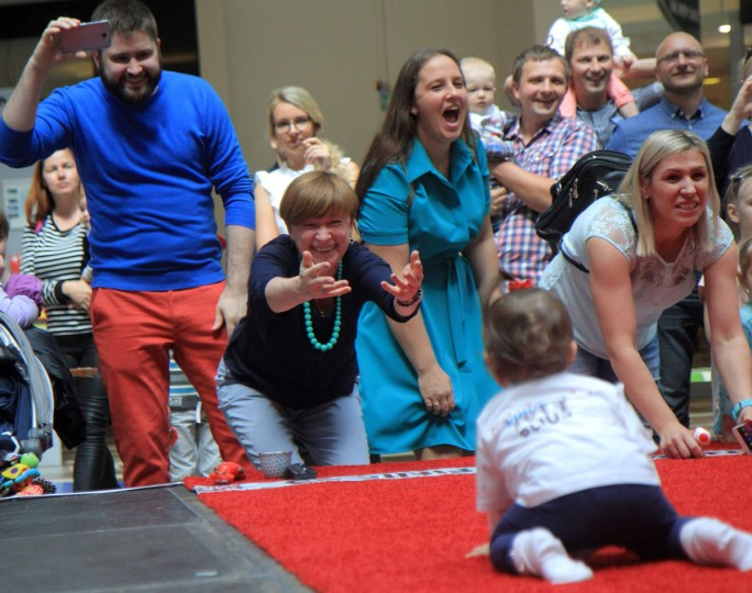 Parents shout encouragement to their babies taking part in a Baby Race to mark international Children Day in Vilnius, Lithuania on June 1, 2017. Ten-month-old Mykolas Pociunas crawled to victory to be crowned Lithuania's fastest toddler, lured across the finish line by a box of Lego plastic bricks. Parents and grandparents waved colourful toys, mobile, phones, balloons, TV remote controls, plastic bottles and even bagels to get their tots across the finish line. (PETRAS MALUKAS/AFP/Getty Images)