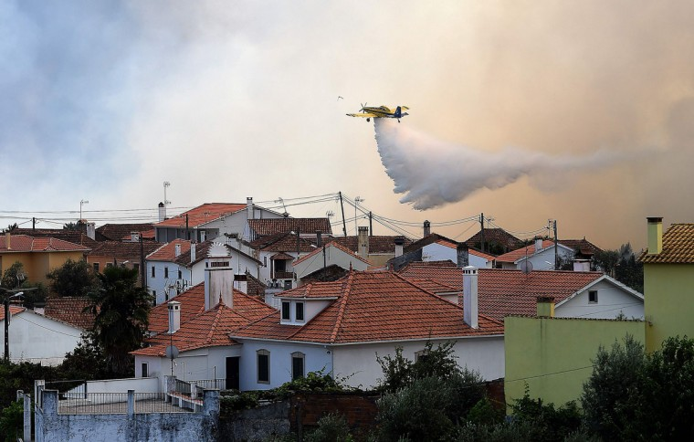A firefighting plane drops a water load over a wildfire in Ouzenda, near Pedrogao Grande on June 20, 2017.The huge forest fire that erupted on June 17, 2017 in central Portugal killed at least 64 people and injured 135 more, with many trapped in their cars by the flames. / (AFP Photo/Francisco Leong)
