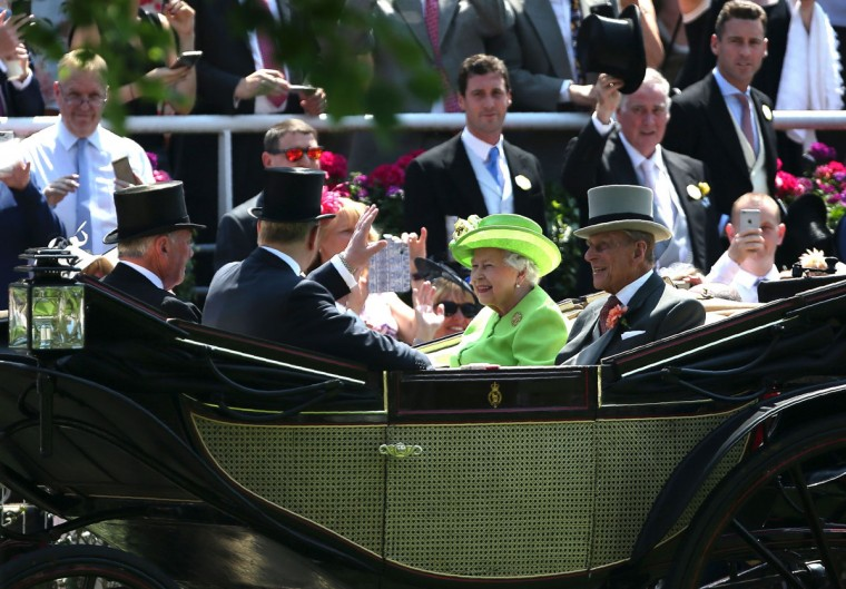 Britain's Queen Elizabeth II (C) and her husband Britain's Prince Philip, Duke of Edinburgh (centtre R) travel by horse-drawn carriage as they arrive on day one of the Royal Ascot horse racing meet, in Ascot, west of London, on June 20, 2017.The five-day meeting is one of the highlights of the horse racing calendar. Horse racing has been held at the famous Berkshire course since 1711 and tradition is a hallmark of the meeting. Top hats and tails remain compulsory in parts of the course while a daily procession of horse-drawn carriages brings the Queen to the course. / (AFP Photo/Daniel Leal-olivas)