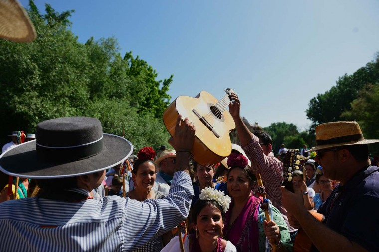 A pilgrim passes a guitar to another as they cross the Quema river during the annual El Rocio pilgrimage in Villamanrique, near Sevilla on June 1, 2017. (CRISTINA QUICLER/AFP/Getty Images)