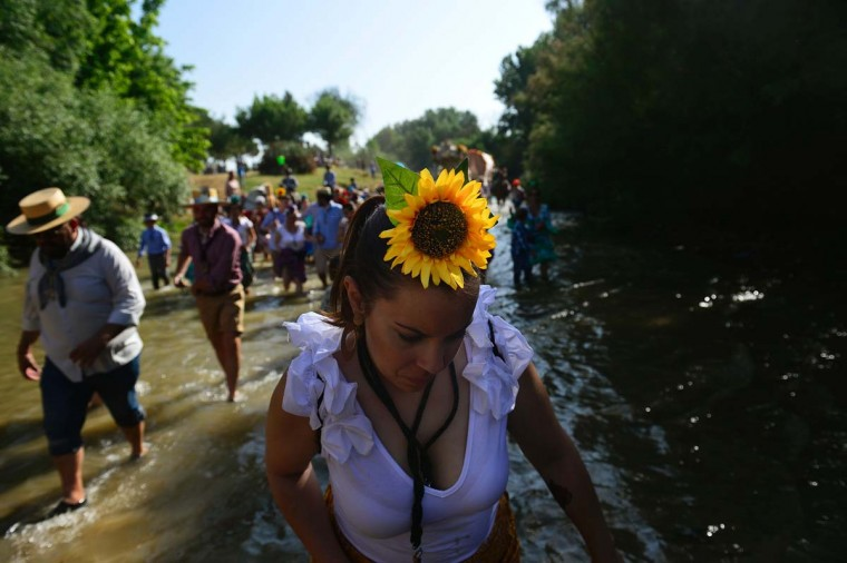 A pilgrim sporting a sunflower crosses the Quema river during the annual El Rocio pilgrimage in Villamanrique, near Sevilla on June 1, 2017. (CRISTINA QUICLER/AFP/Getty Images)