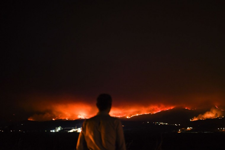 A man stands on the roadside and watches a wildfire at Anciao, Leiria, central Portugal, on June 18, 2017. A wildfire in central Portugal killed at least 25 people and injured 16 others, most of them burning to death in their cars, the government said on June 18, 2017. Several hundred firefighters and 160 vehicles were dispatched late on June 17 to tackle the blaze, which broke out in the afternoon in the municipality of Pedrogao Grande before spreading fast across several fronts. / (AFP Photo/Patricia Melo moreirapatricia de melo moreira)