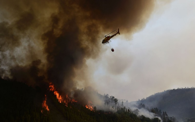 A helicopter overfly a wildfire in Carvalho, next to Pampilhosa da Serra, on June 19, 2017.More than 1,000 firefighters are still trying to control the huge forest fire that erupted on June 17, 2017 in central Portugal killing at least 62 people and injuring 62 more, many trapped in their cars by the flames, causing a great deal of emotion in the country. / (AFP Photo/Miguel Riopa)