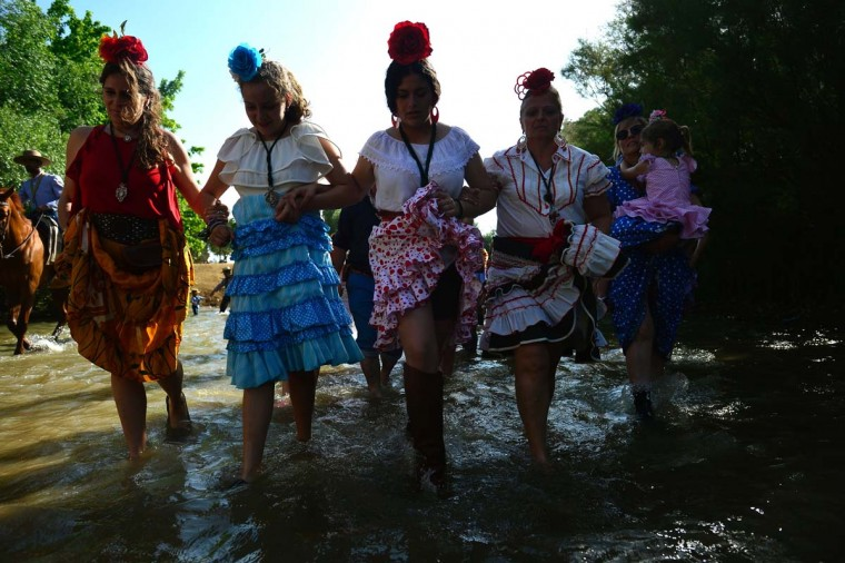 Pilgrims lift up their dresses as they cross the Quema river during the annual El Rocio pilgrimage in Villamanrique, near Sevilla on June 1, 2017. (CRISTINA QUICLER/AFP/Getty Images)