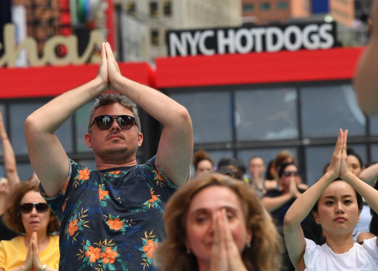 People take part in the 15th annual Times Square yoga event celebrating the Summer Solstice, the longest day of the year, during classes in the middle of Times Square on June 21, 2017 in New York. The event marked the international day of yoga. / (AFP Photo/Timothy Clarytimothy a. clary)