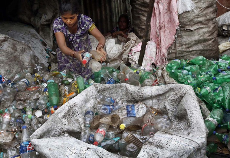An Indian woman worker sorts used plastic bottles at a recycling unit in Mumbai, India, Friday, June 5, 2015. The World Environment Day is celebrated on June 5 every year by the United Nations for encouraging worldwide awareness and action for the environment. (AP Photo/Rajanish Kakade)