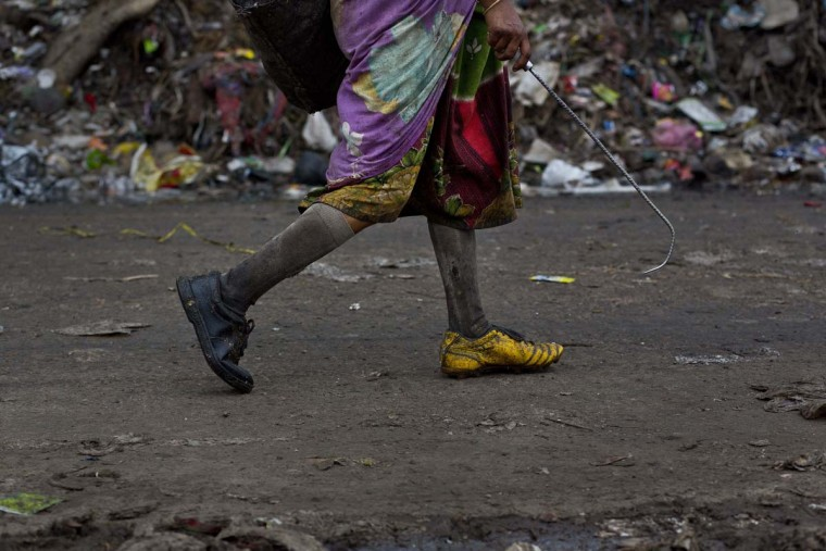 An Indian ragpicker woman walks searching for recyclable materials at a garbage dumping site on the outskirts of Gauhati, Assam state, India, Monday, June 5, 2017. Monday marks World Environment Day. (AP Photo/Anupam Nath)