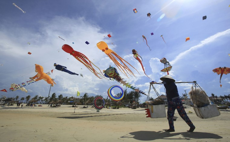 In this Sunday, June 11, 2017, photo, a food vendor walks under flying kites on Tam Thanh beach during an International Kite Festival in Quang Nam province, Vietnam. Hundreds of flying giant sea creatures, animal shaped and folklore inspired kites from 20 countries were taken to the sky. (AP Photo/Hau Dinh)