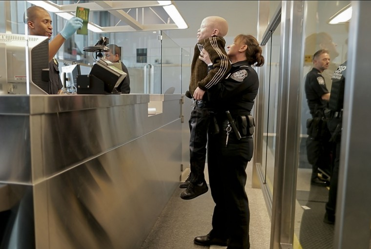Baraka Cosmas, 7, is helped by a Customs Border and Patrol agent upon arriving at JFK airport from Tanzania, Saturday, March 25, 2017, in New York. Cosmas was returning to the United States along with three other albinos to be refitted for new prosthetic limbs for their growing bodies. The four, all albinos, lost limbs to attackers who believe body parts from albinos hold magical powers. (AP Photo/Julie Jacobson)