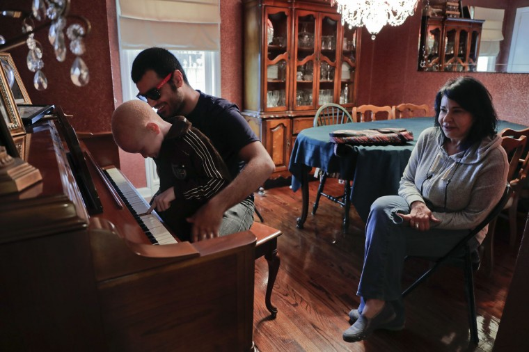 Global Medical Relief Fund founder Elissa Montanti, right, listens as Baraka Cosmas, left, follows instructions from Ahmed Shareef, as they play on a piano at a friend's home, Sunday, June 4, 2017, in Staten Island, N.Y. Both Cosmas and Shareef are amputees from the elbow down. Cosmas, who is afflicted with albinism has severely limited eyesight and Shareef is blind. (AP Photo/Julie Jacobson)