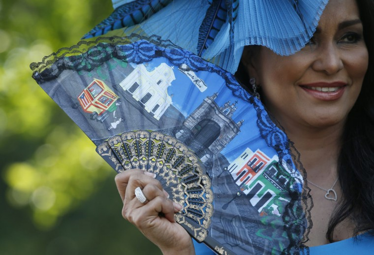 A racegoer uses a fan posing for photographers as she arrives for the first day of the Royal Ascot horse race meeting in Ascot, England, Tuesday, June 20, 2017. (AP Photo/Alastair Grant)