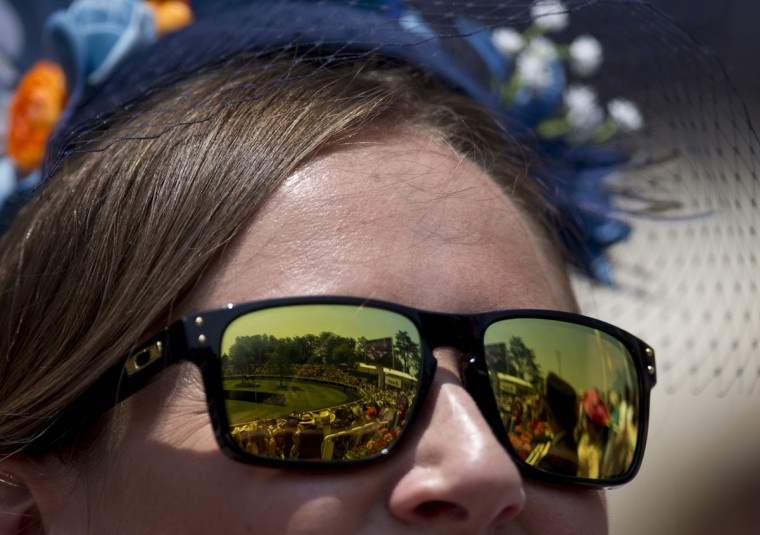 A racegoer watches the parade ring prior to the arrival of Britain's Queen Elizabeth II on the first day of the Royal Ascot horse race meeting in Ascot, England, Tuesday, June 20, 2017. (AP Photo/Alastair Grant)