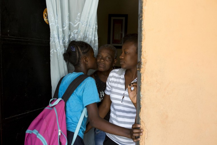 In this May 26, 2017 photo, 13-year-old Medege Dorlus greets the family she now lives with as she arrives from school in Port-au-Prince, Haiti. Medege says that she feels okay with her new home but also that she has no other option since her mother died and left her homeless. (AP Photo/Dieu Nalio Chery)