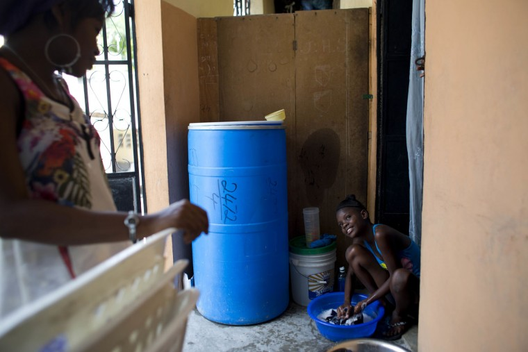 In this May 27, 2017 photo, Stephan, left, talks to 13-year-old Medege Dorlus, who washes Stephan' clothes at their home in Port-au-Prince, Haiti. Medege cooks, cleans, does laundry and goes shopping for the household. (AP Photo/Dieu Nalio Chery)