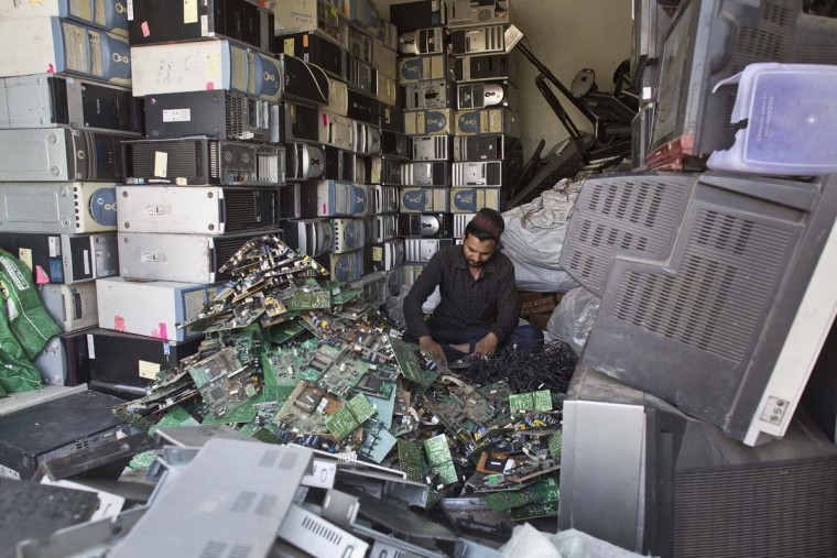 An Indian man works at a electronic waste recycling shop on World Environment Day in Gauhati, Assam state, India, Monday, June 5, 2017. (AP Photo/ Anupam Nath)