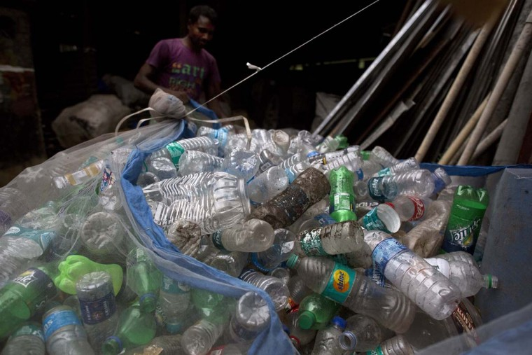 An Indian ragpicker man ties a net full of plastic bottles on the outskirts of Gauhati, Assam state, India, Monday, June 5, 2017. Monday marks World Environment Day. (AP Photo/Anupam Nath)