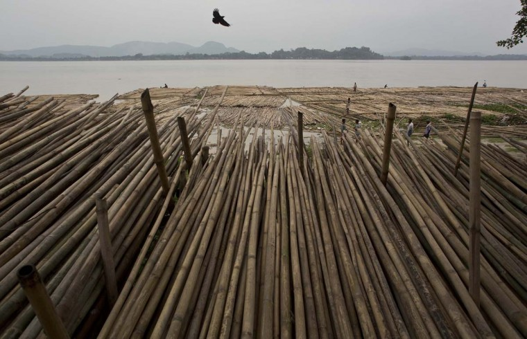 Indian laborers bring loads of bamboo through the River Brahmaputra to a whole sale bamboo market by the river in Gauhati, Assam state, India, Monday, June 5, 2017. Monday marks World Environment Day. (AP Photo/Anupam Nath)