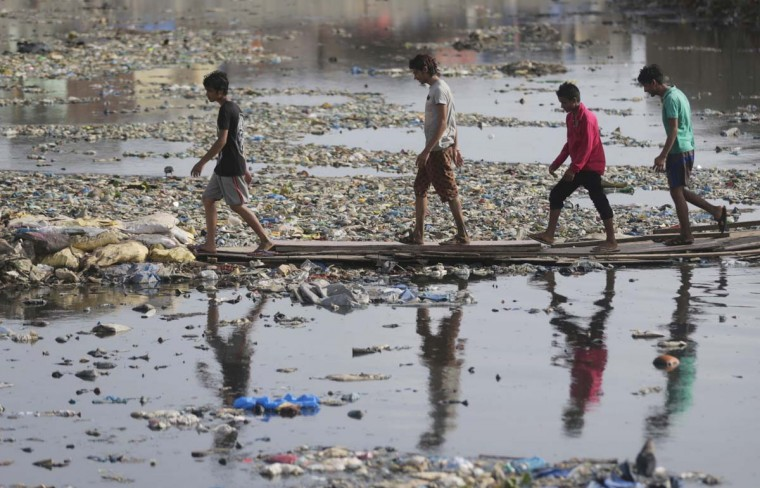 Indian men walk through a water canal polluted with plastic and other garbage in Mumbai, India, Monday, June 5, 2017. Monday marks the World Environment Day. (AP Photo/Rafiq Maqbool)