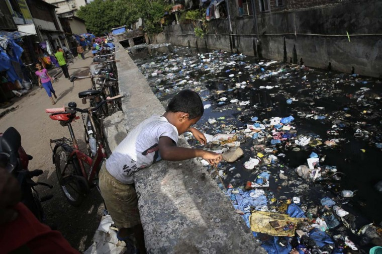 An Indian boy tries to collect copper wires with a rope from a water canal polluted with plastic and other garbage in Mumbai, India, Monday, June 5, 2017. Monday marks the World Environment Day. (AP Photo/Rafiq Maqbool)