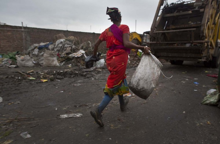 An Indian ragpicker woman runs behind a dumper truck that arrives to unload garbage at a garbage dumping site on the outskirts of Gauhati, Assam state, India, Monday, June 5, 2017. Monday marks World Environment Day. (AP Photo/Anupam Nath)