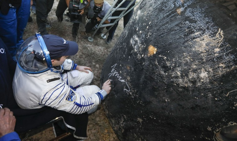 Member of the International Space Station crew French astronaut Thomas Pesquet signs the Soyuz landing capsule after landing in a remote area outside the town of Dzhezkazgan, Kazakhstan, Friday, June 2, 2017. The capsule with Russian cosmonaut Oleg Novitsky and French astronaut Thomas Pesquet, landed Friday on the steppes of Kazakhstan. (Shamil Zhumatov/Pool Photo via AP)