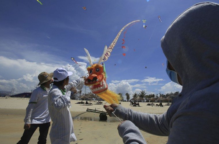 In this Sunday, June 11, 2017, photo, flyers control a dragon kite on Tam Thanh beach during an International Kite Festival in Quang Nam province, Vietnam. Hundreds of flying giant sea creatures, animal shaped and folklore inspired kites from 20 countries were taken to the sky. (AP Photo/Hau Dinh)