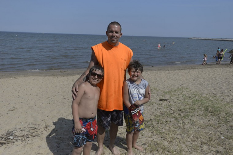 Raymond Averella of Water's Edge, Maryland, with his sons Giuseppe and Luke. Averella said they come to North Point about three times a week. The water's warm, said Averella. (Christina Tkacik/Baltimore Sun)