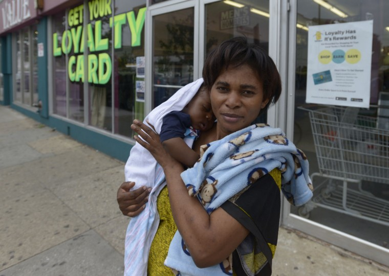 Bora Mounesh, originally from Congo, stands with her sleeping baby on Eastern Avenue in Highlandtown. The diverse neighborhood is home to several organizations that help immigrants and refugees establish lives in the United States, including the International Refugee Committee. (Christina Tkacik/Baltimore Sun)