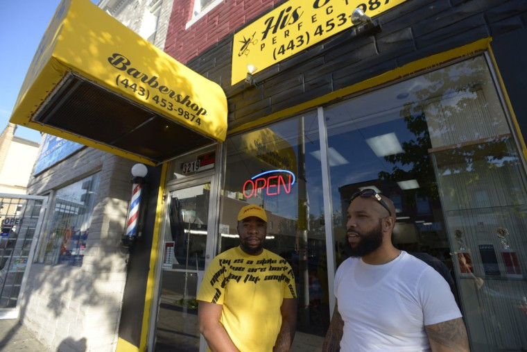 "Devin Fowlkes, left, manager His & Her Perfections Barbershop, praised the diversity of the neighborhood. ""Like me, I'm Afro-Latino."" (Christina Tkacik/Baltimore Sun)"