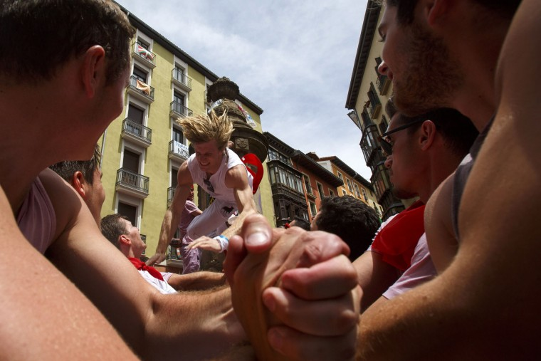 A reveller jumps from a fountain at Navarreria Street as people enjoy the atmosphere during the opening day or 'Chupinazo' of the San Fermin Running of the Bulls fiesta on July 6, 2017 in Pamplona, Spain. The annual Fiesta de San Fermin, made famous by the 1926 novel of US writer Ernest Hemingway entitled 'The Sun Also Rises', involves the daily running of the bulls through the historic heart of Pamplona to the bull ring. (Photo by Pablo Blazquez Dominguez/Getty Images)