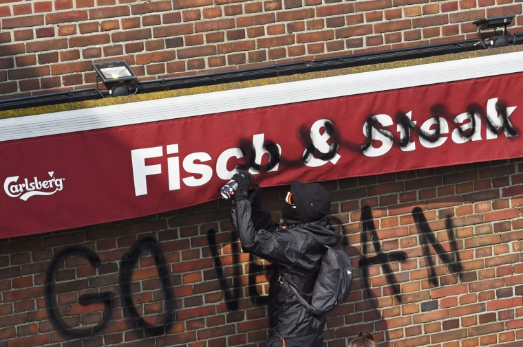 "A protester sprays ""Go Vegan"" on a fish and steak shop on July 7, 2017 in Hamburg, northern Germany, where leaders of the world's top economies gather for a G20 summit.Protesters clashed with police and torched patrol cars in fresh violence ahead of the G20 summit, police said. German police and protestors had clashed already the day before at an anti-G20 march, with police using water cannon and tear gas to clear a hardcore of masked anti-capitalist demonstrators, AFP reporters said. / (AFP Photo/Christof Stache)"