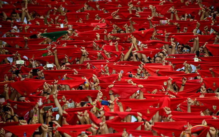 Participants hold red scarves as they celebrate the 'Chupinazo' (start rocket) to mark the kickoff at noon sharp of the San Fermin Festival, in front of the Town Hall of Pamplona, northern Spain, on July 6, 2017. A red-and-white sea of revellers soaked each other with wine in a packed Pamplona square today to kick off Spain's most famous fiesta, the San Fermin bull-running festival. (Miguel Riopa/AFP/Getty Images)
