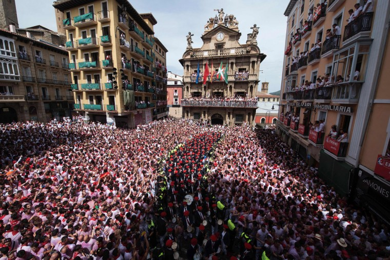 "The ""Pamplonesa"" municipal music band performs during the launch of the 'Chupinazo' (start rocket) to mark the kickoff at noon sharp of the San Fermin Festival, in front of the Town Hall of Pamplona, northern Spain, on July 6, 2017. A red-and-white sea of revellers soaked each other with wine in a packed Pamplona square today to kick off Spain's most famous fiesta, the San Fermin bull-running festival. (Ander Gillenea/AFP/Getty Images)"