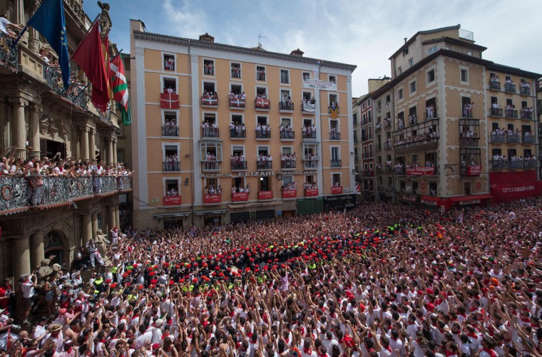 Participants celebrate the 'Chupinazo' (start rocket) to mark the kickoff at noon sharp of the San Fermin Festival, in front of the Town Hall of Pamplona, northern Spain, on July 6, 2017. A red-and-white sea of revellers soaked each other with wine in a packed Pamplona square today to kick off Spain's most famous fiesta, the San Fermin bull-running festival. (Miguel Riopa/AFP/Getty Images)