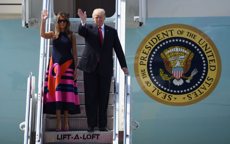 US President Donald Trump and US First Lady Melania Trump wave as they step off Air Force One upon arrival at the airport in Hamburg, northern Germany on July 6, 2017. Leaders of the world's top economies will gather from July 7 to 8, 2017 in Germany for likely the stormiest G20 summit in years, with disagreements ranging from wars to climate change and global trade. / (AFP Photo/Christof Stache)