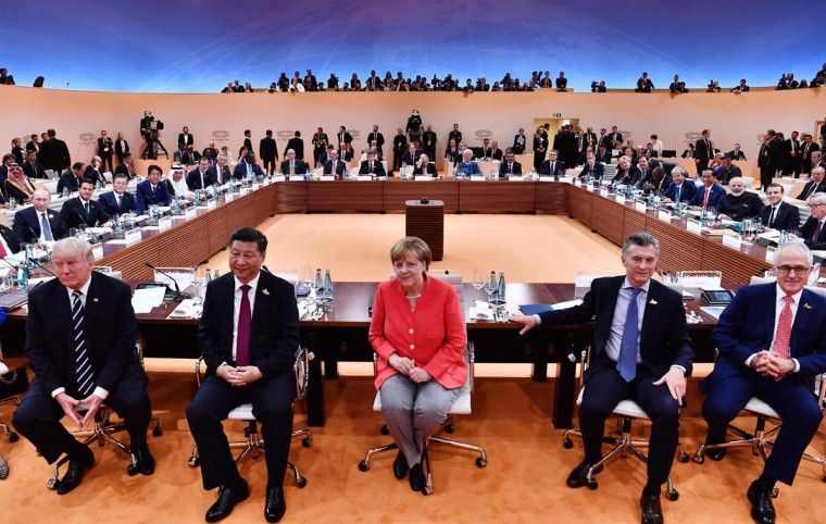 (L-R) US President Donald Trump, China's President Xi Jinping, German Chancellor Angela Merkel, Argentinia's President Mauricio Macri and Australia's Prime Minister Malcolm Turnbull turn around for photographers at the start of the first working session of the G20 meeting in Hamburg, northern Germany, on July 7.Leaders of the world's top economies will gather from July 7 to 8, 2017 in Germany for likely the stormiest G20 summit in years, with disagreements ranging from wars to climate change and global trade. / (AFP Photo/Afp And pool )