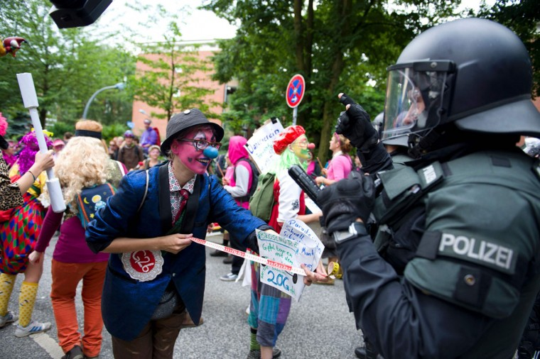 "Demonstrators dressed as clowns face policemen as they take part in a protest titled ""#BlockG20 - Color the Red Zone"" on July 7, 2017 in Hamburg, northern Germany, where leaders of the world's top economies gather for a G20 summit.Protesters clashed with police and torched patrol cars in fresh violence ahead of the G20 summit, police said. German police and protestors had clashed already on Thursday (July 6, 2017) at an anti-G20 march, with police using water cannon and tear gas to clear a hardcore of masked anti-capitalist demonstrators, AFP reporters said. / (AFP Photo/Dpa / )"