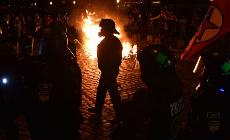"Police officers walk in front of a fire started by protesters the ""Welcome to Hell"" rally against the G20 summit in Hamburg, northern Germany on July 6, 2017. Leaders of the world's top economies will gather from July 7 to 8, 2017 in Germany for likely the stormiest G20 summit in years, with disagreements ranging from wars to climate change and global trade. / (AFP Photo/Christof Stache)"