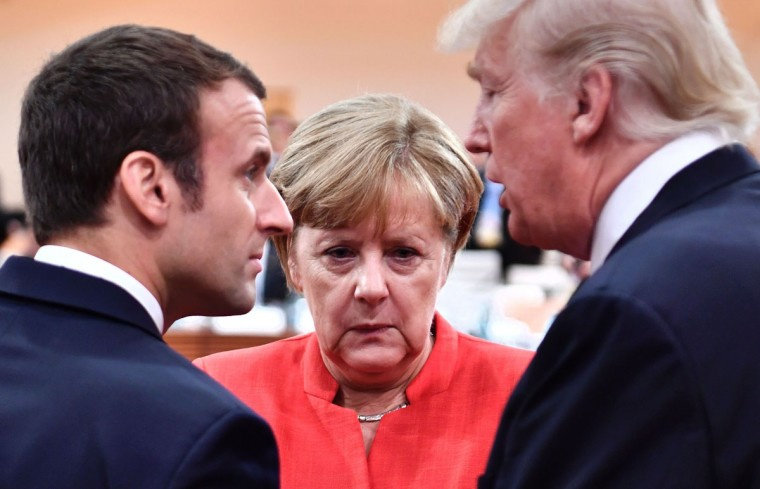 (L-R) French President Emmanuel Macron, German Chancellor Angela Merkel and US President Donald Trump confer at the start of the first working session of the G20 meeting in Hamburg, northern Germany, on July 7.Leaders of the world's top economies will gather from July 7 to 8, 2017 in Germany for likely the stormiest G20 summit in years, with disagreements ranging from wars to climate change and global trade. / (AFP Photo/Afp And pool )