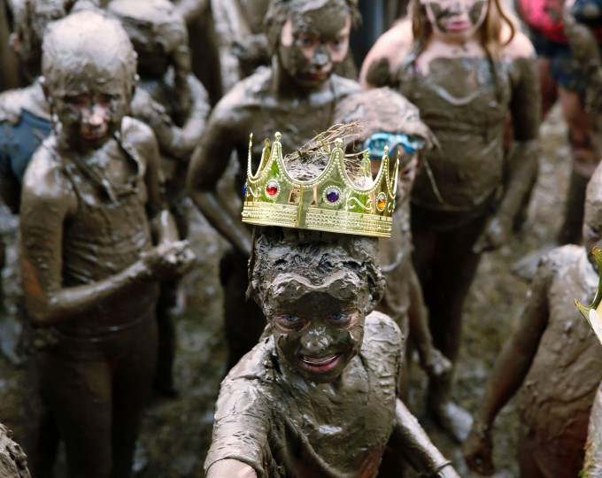 Mackenna Kofahl, 12, of Redford looks up after being crowned Mud Day Queen as part of Wayne County's annual Mud Day at Nankin Mills Park on July 11, 2017 in Westland, Michigan. The mud pit contains 200 tons (181 metric tons) of top soil and 20,000 gallons (75,708 liters) of water. (Jeff Kowalsky/AFP/Getty Images)