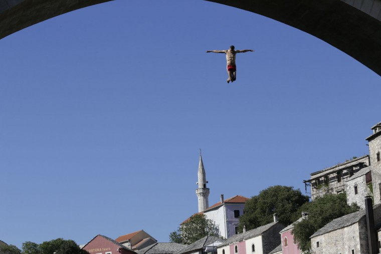 A diver drops through the air from the Mostar bridge during 451th traditional annual high diving competition, in Mostar, 140 kms south of Bosnian capital of Sarajevo, Sunday, July 30, 2017. Total of 41 divers from Bosnia and neighbouring countries competed diving from 25 meters high Old Mostar Bridge into the Neretva river. (AP Photo/Amel Emric)